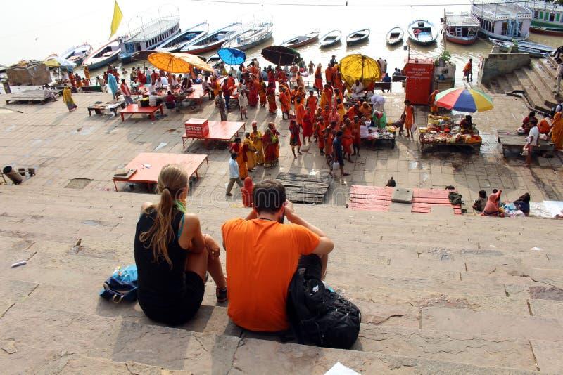 Übersetzung: Touristen, die beschäftigte vorbereitende Rituale der lokalen Leute bei Assi Ghat in Varanasi durch den Ganges aufpa lizenzfreie stockfotografie