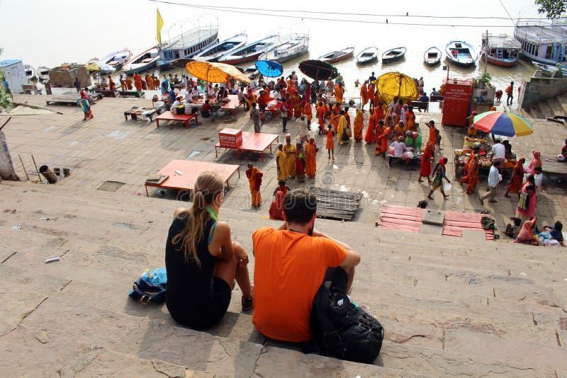 Übersetzung: Touristen, die beschäftigte vorbereitende Rituale der lokalen Leute bei Assi Ghat in Varanasi durch den Ganges aufpa stockbilder