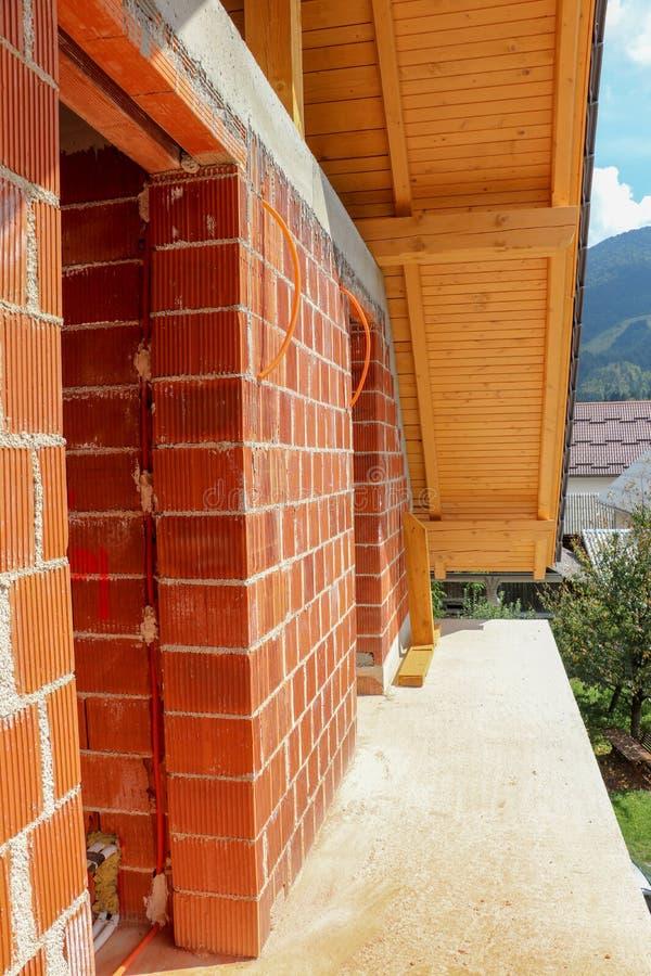 Übertragen Sie Wand mit elektrischem cablesbalcony mit Dach in unfertigem Haus stockfotografie