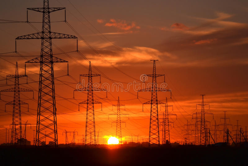 Übertragungszeilen des Stroms am Sonnenuntergang stockbild