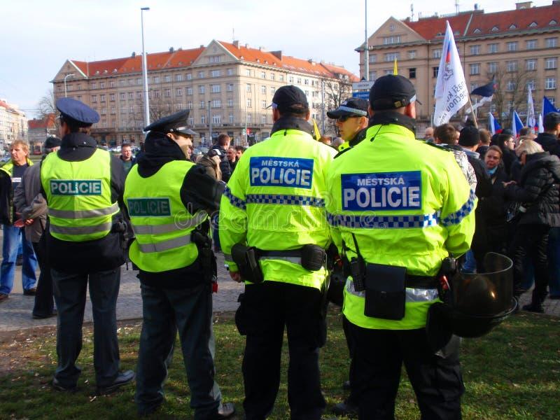 Überwachen Sie aufpassende Protestantvölker gegen Migranten in der Hauptstadt der Tschechischen Republik Prag polizeilich lizenzfreie stockfotos