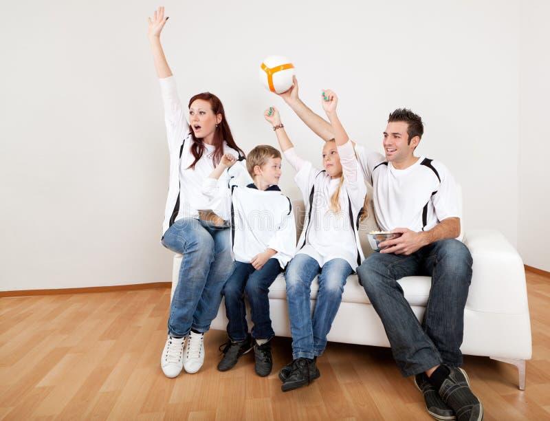 Überwachende Fußbalabgleichung der jungen Familie zu Hause lizenzfreie stockfotos