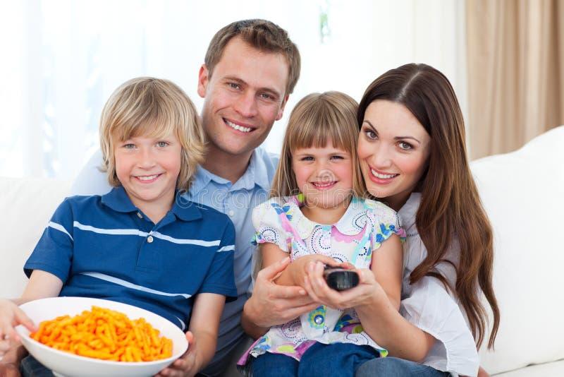 Überwachendes Fernsehen der glücklichen Familie und essen Chips stockfoto