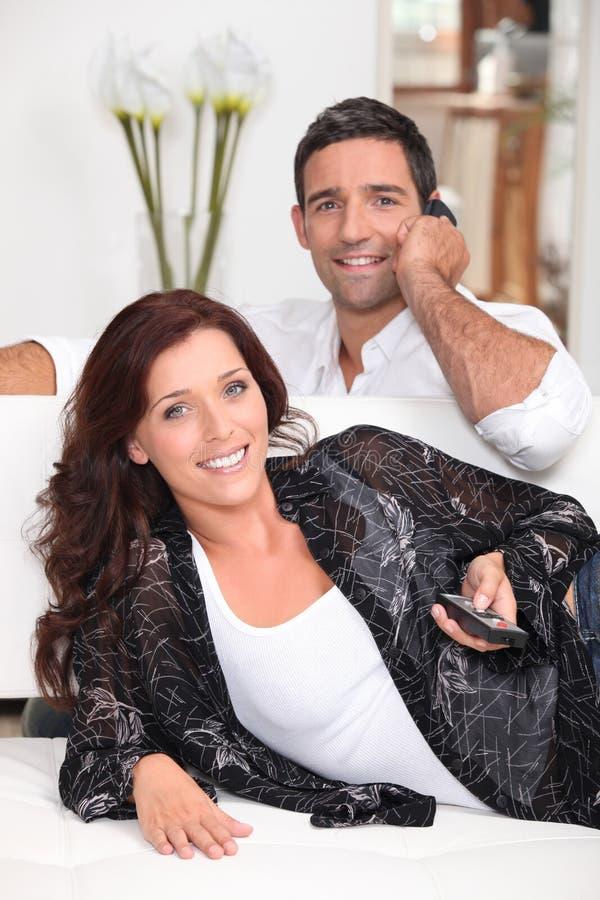 Überwachendes Fernsehen der Paare stockbild