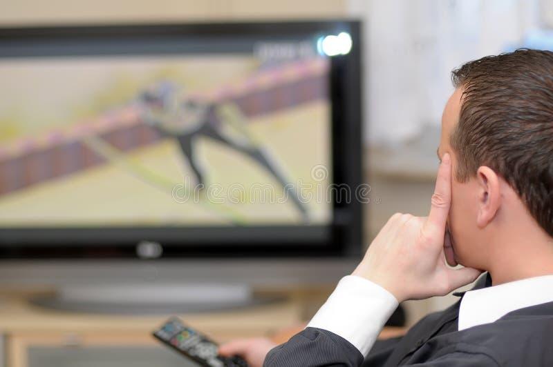 Überwachendes Fernsehen des Mannes. lizenzfreies stockbild