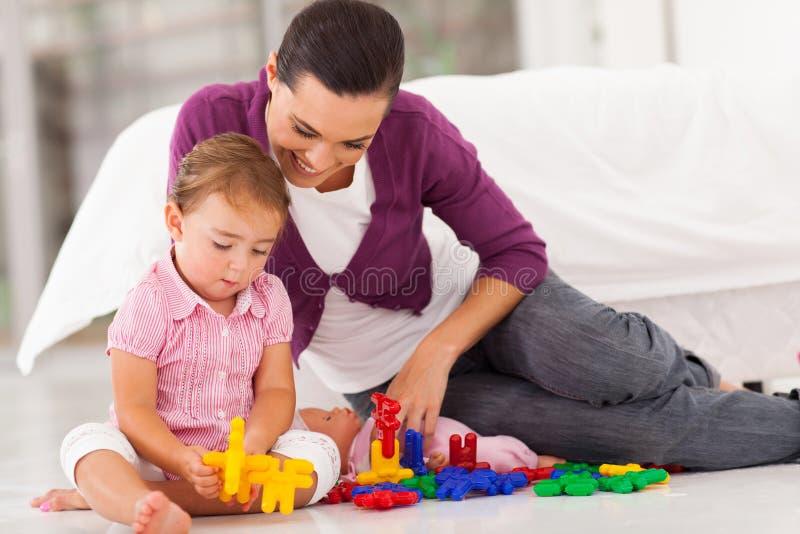 Überwachendes Tochterspielen der Mutter stockfotografie