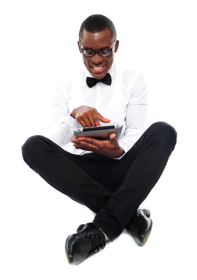 Überwachendes Video des afrikanischen Jungen auf Tablette-PC stockfotografie