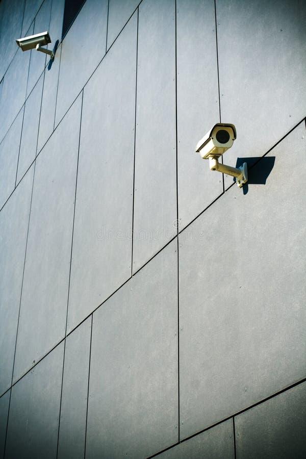 Überwachungskamera auf dunklem Gebäudehintergrund lizenzfreies stockfoto