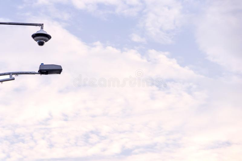 Überwachungskamera im Himmel mit vielen Wolken bei Sonnenuntergang mit Stadtlampe stockfoto