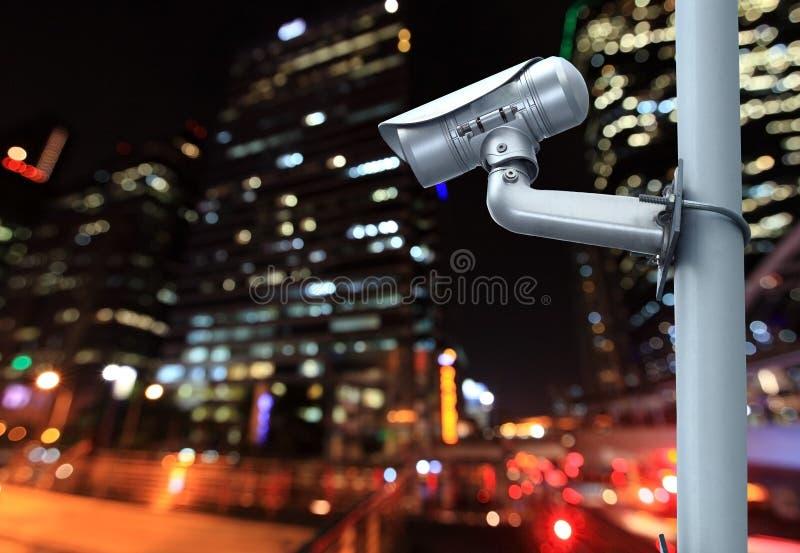 Überwachungskamera mit dem Verwischen der Nachtstadt im Hintergrund stockfotografie