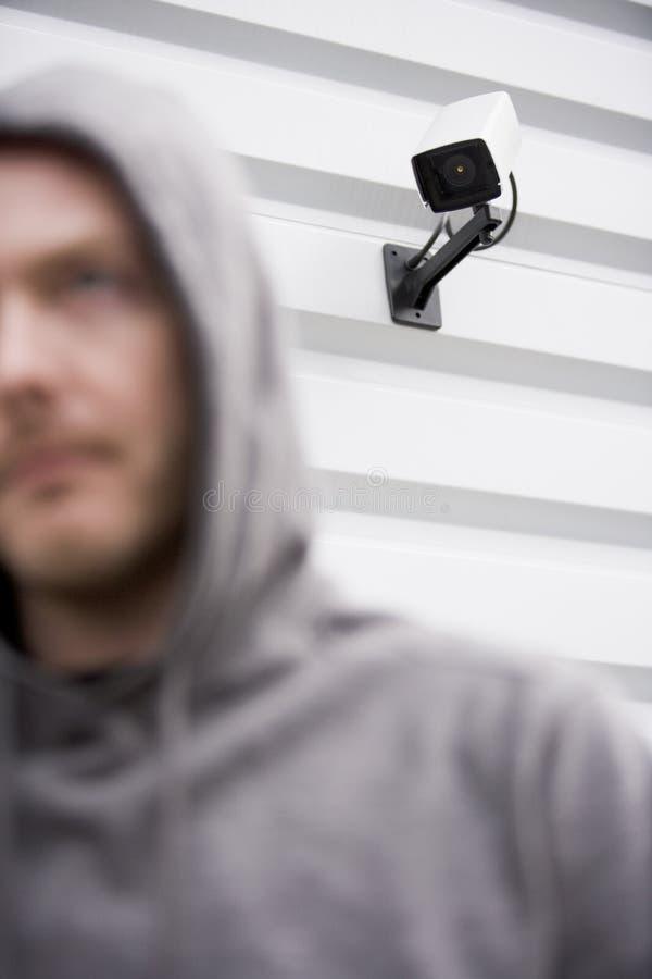 Überwachungskamera und Mann im mit Kapuze Sweatshirt stockfotos