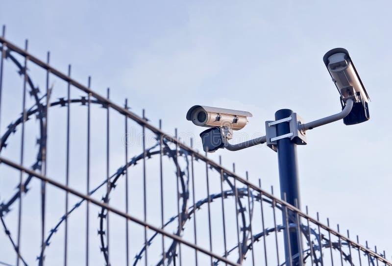 Überwachungskameras über Zaun stockbild