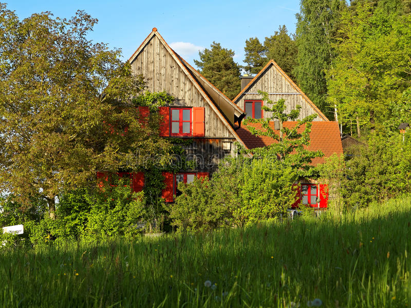 Überwuchertes Holzhaus am Frühling lizenzfreie stockbilder