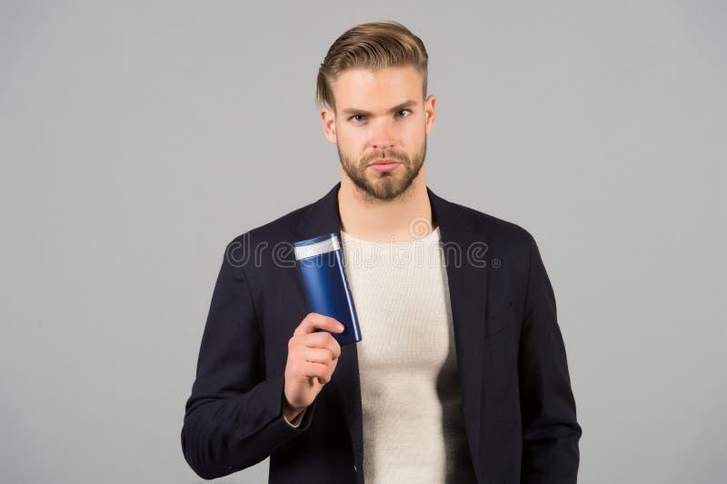 Überzeugt im Haarpflegeprodukt Stilvolle Frisur des Mannes hält Produkt-Grauhintergrund der Flasche hygienischen Schalten Sie Lec lizenzfreie stockfotografie