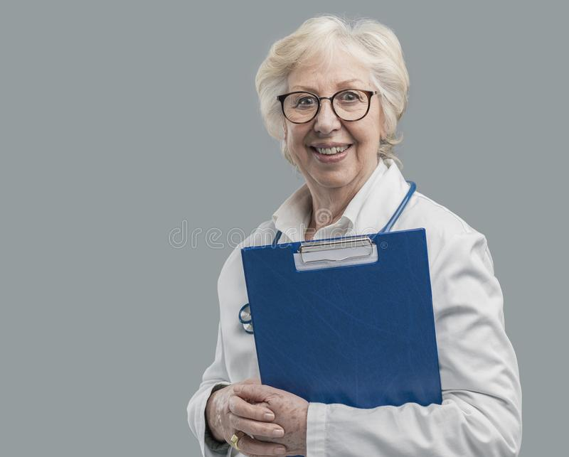 Überzeugte ältere aufwerfende und lächelnde Ärztin lizenzfreie stockbilder
