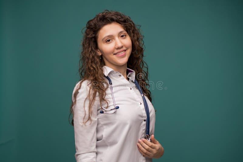 Überzeugte Ärztin, die am Kamera-, Gesundheitswesen- und Verhinderungskonzept, auf grünem Hintergrund, Kopienraum lächelt stockbild