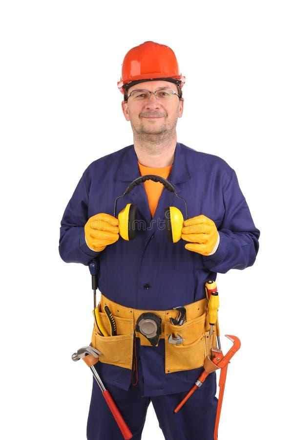 Überzeugte Arbeitskraft in den Ohrmuffen und -gläsern. stockbilder