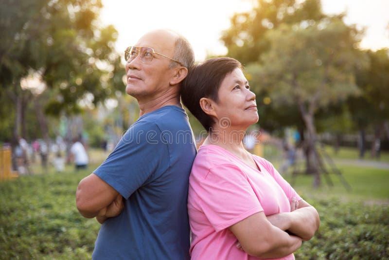 Überzeugte asiatische ältere Leute, die mit den Armen gekreuzt aufwerfen stockbilder