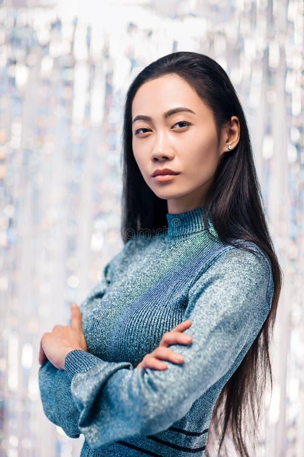 Überzeugte asiatische Frau im blauen Kleid mit den gekreuzten Armen lizenzfreies stockbild