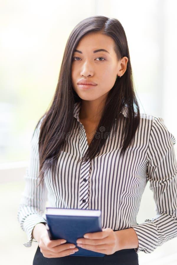 Überzeugte asiatische Geschäftsfrau mit Notizbuch lizenzfreie stockfotos