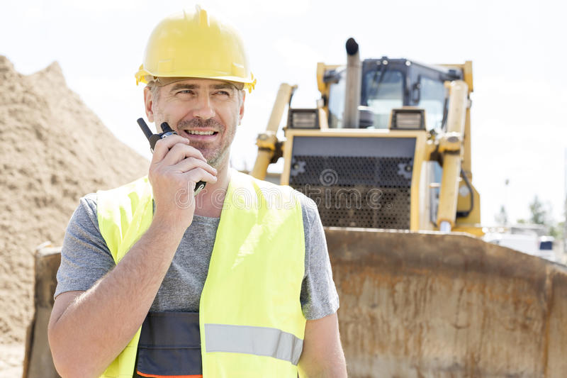 Überzeugte Aufsichtskraft, die Funksprechgerät an der Baustelle verwendet lizenzfreie stockfotografie