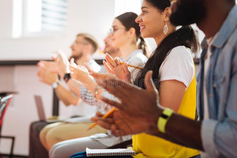 Überzeugte beim Applaudieren in Folge sitzende und lächelnde Studenten stockfoto