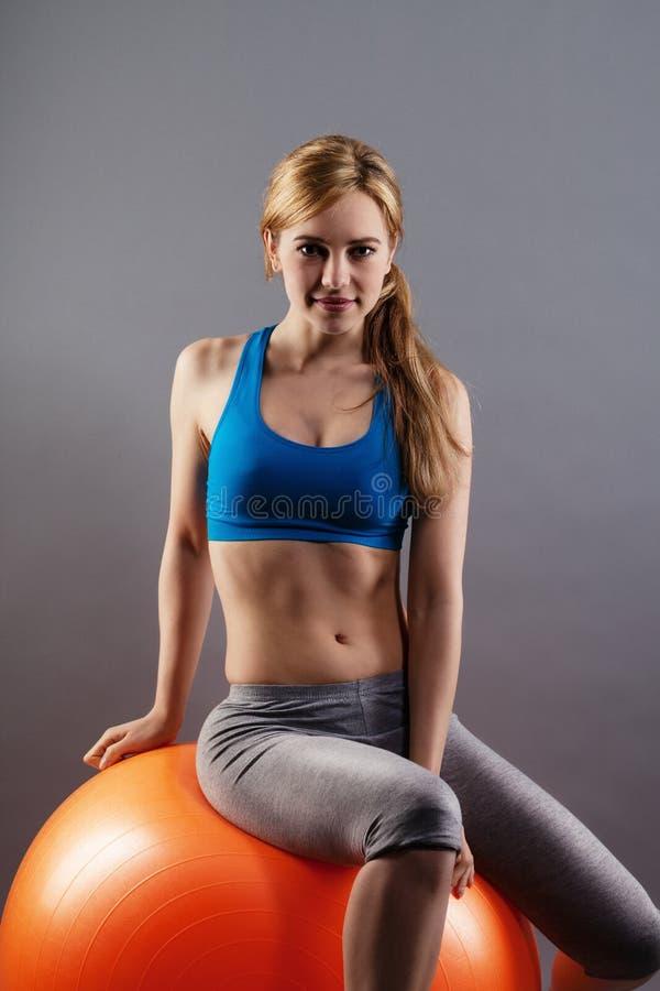 Überzeugte Eignungsfrau, die auf einer orange Übungskugel sitzt stockbild