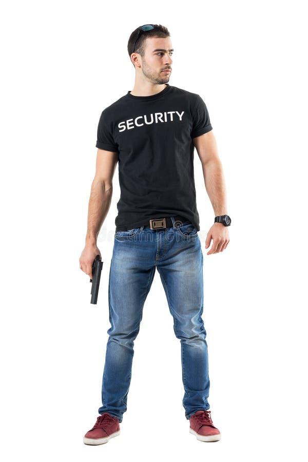 Überzeugte einfache Kleidungsmachospindel mit dem Gewehr, das weg vorsichtig schaut stockbilder