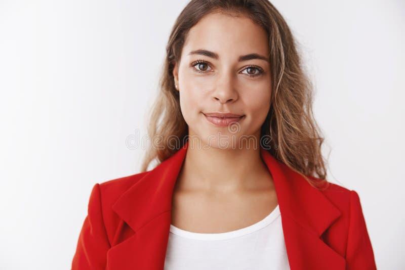 Überzeugte erfolgreiche schöne glückliche junge gelockte moderne Geschäftsfrau des Porträts, die lächelnden Selbst der roten Jack lizenzfreie stockfotos