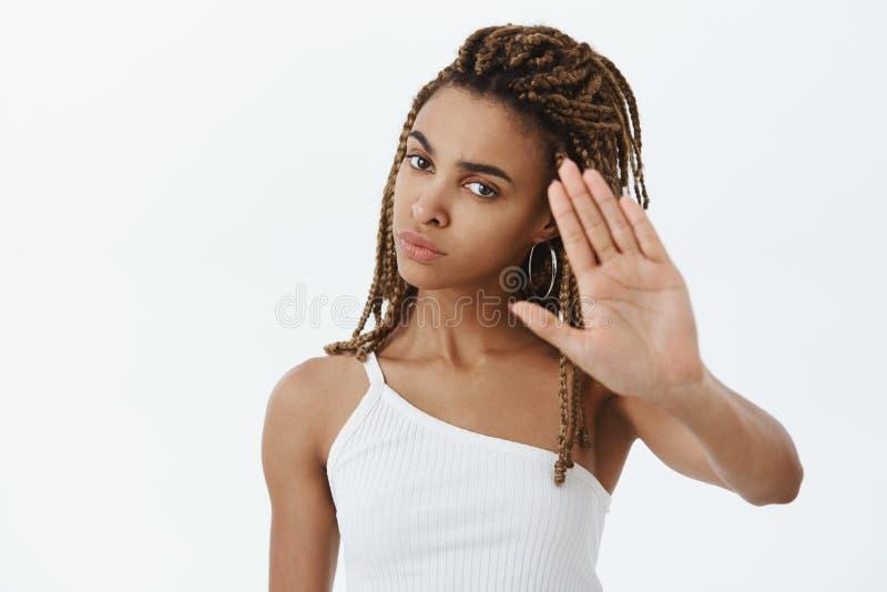 Überzeugte ernst-aussehende missfallene und gestörte Afroamerikanerfrau mit den Dreadlocks, die Palmen anheben, um zu sinken und  lizenzfreies stockfoto