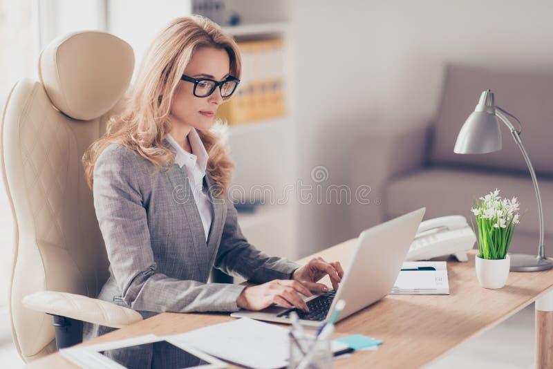 Überzeugte ernste erfahrene qualifizierte schöne intelligente Frau wi stockfotos