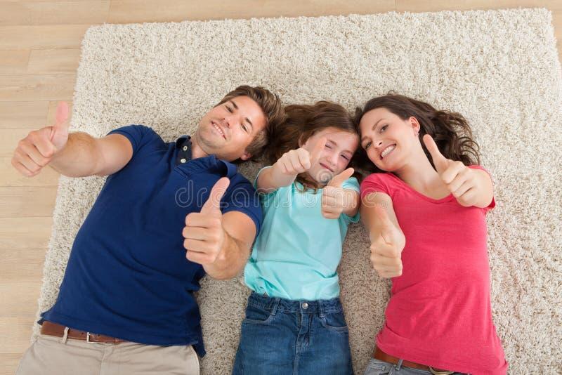 Überzeugte Familie, die oben Daumen zu Hause gestikuliert stockbilder
