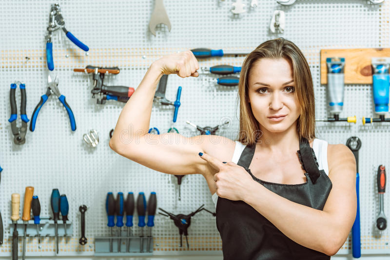 Überzeugte Frau, die ihr Bizeps in der Werkstatt demonstriert stockfoto