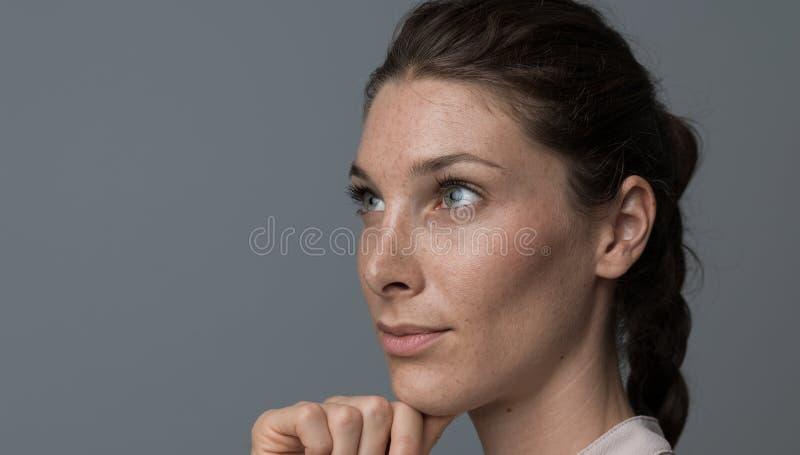 Überzeugte Frau, die mit der Hand auf Kinn denkt stockbild