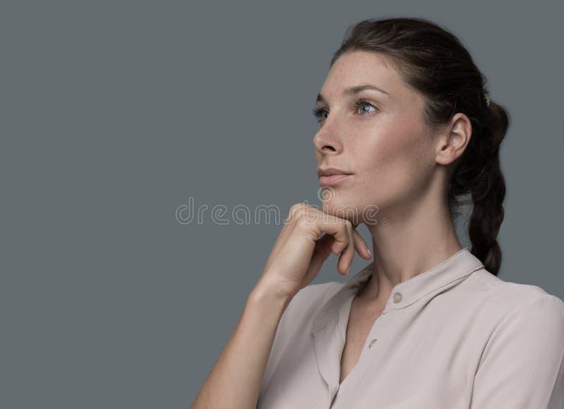 Überzeugte Frau, die mit der Hand auf Kinn denkt lizenzfreie stockbilder