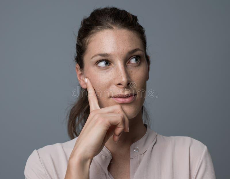 Überzeugte Frau, die mit der Hand auf Kinn denkt stockfotos