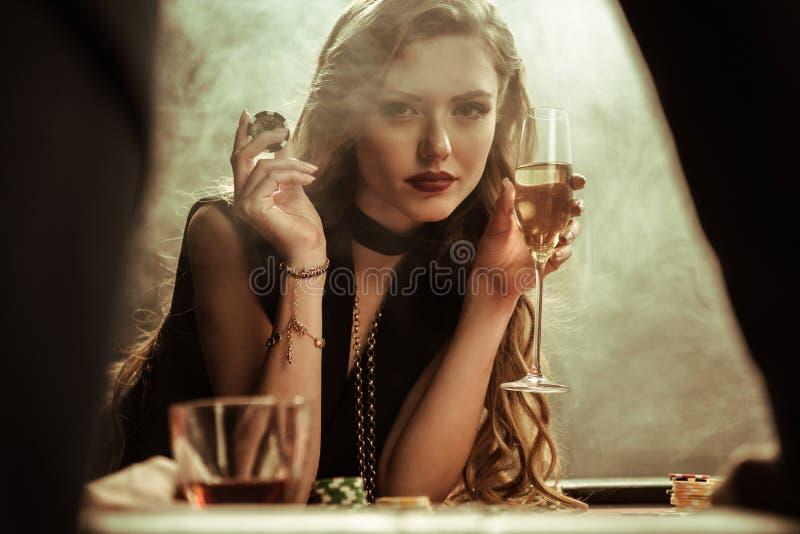 Überzeugte Frau mit Getränk und Pokerchip in den Händen stockfotografie