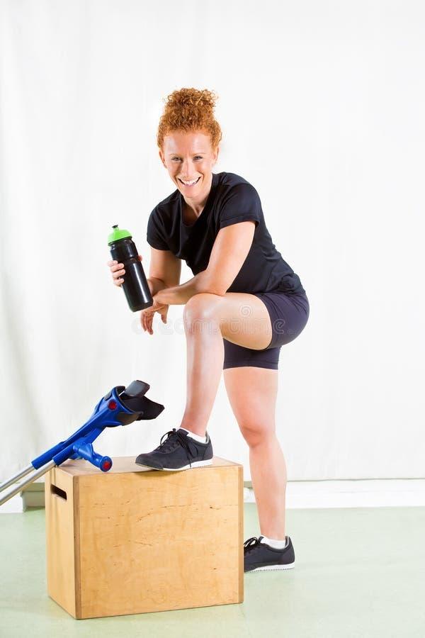 Überzeugte Frau mit Krücken und dem geheilten Bein stockfoto