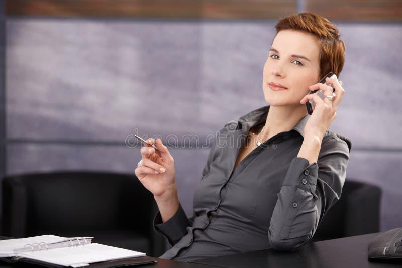 Überzeugte Geschäftsfrau beim Telefonaufruf lizenzfreies stockbild