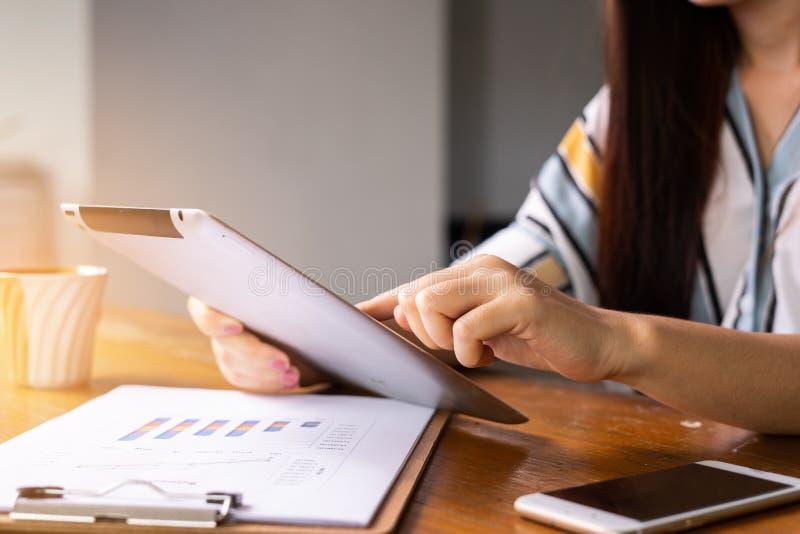 Überzeugte Geschäftsfrau in der intelligenten Freizeitkleidung, die an intelligentem Telefon beim Sitzen im kreativen Büro arbeit stockbild