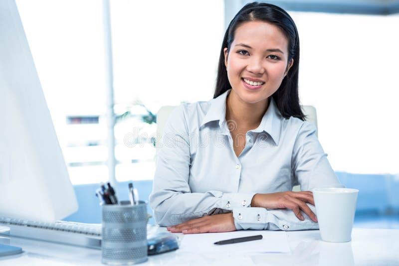 Überzeugte Geschäftsfrau, die auf dem Schreibtisch aufwirft für Kamera sitzt lizenzfreies stockbild