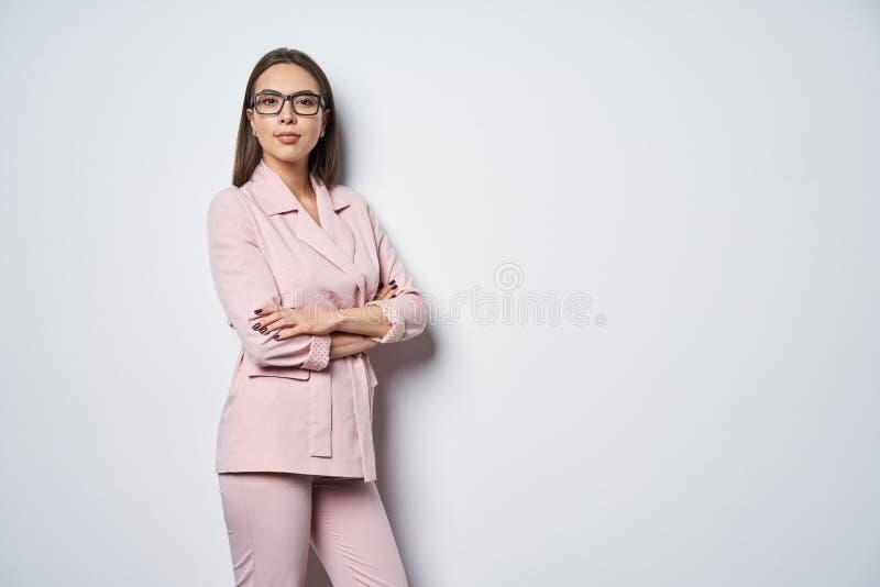 Überzeugte Geschäftsfrau, die bereitstehende weiße Wand des rosa Anzugs mit den gefalteten Händen trägt lizenzfreie stockbilder