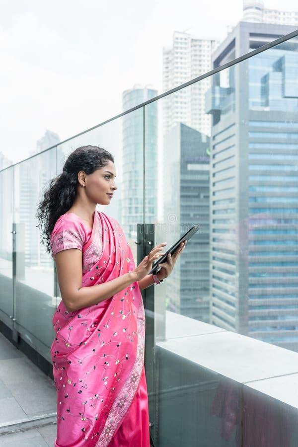 Überzeugte Geschäftsfrau, die draußen einen Tablet-PC verwendet lizenzfreies stockbild