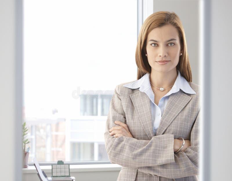 Überzeugte Geschäftsfrau, die im hellen Büro lächelt lizenzfreie stockbilder