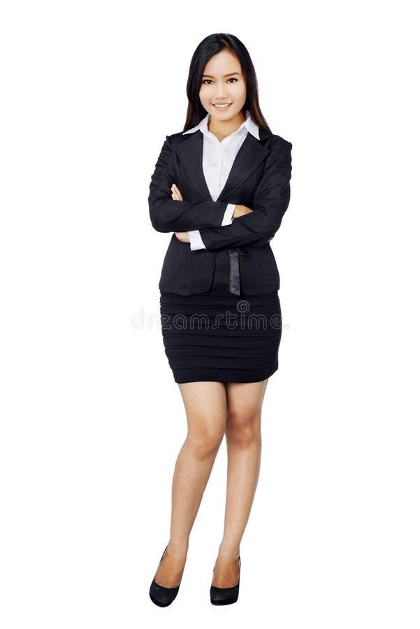 Überzeugte Geschäftsfrau, die im schwarzen Anzug in voller Länge steht. stockfotografie