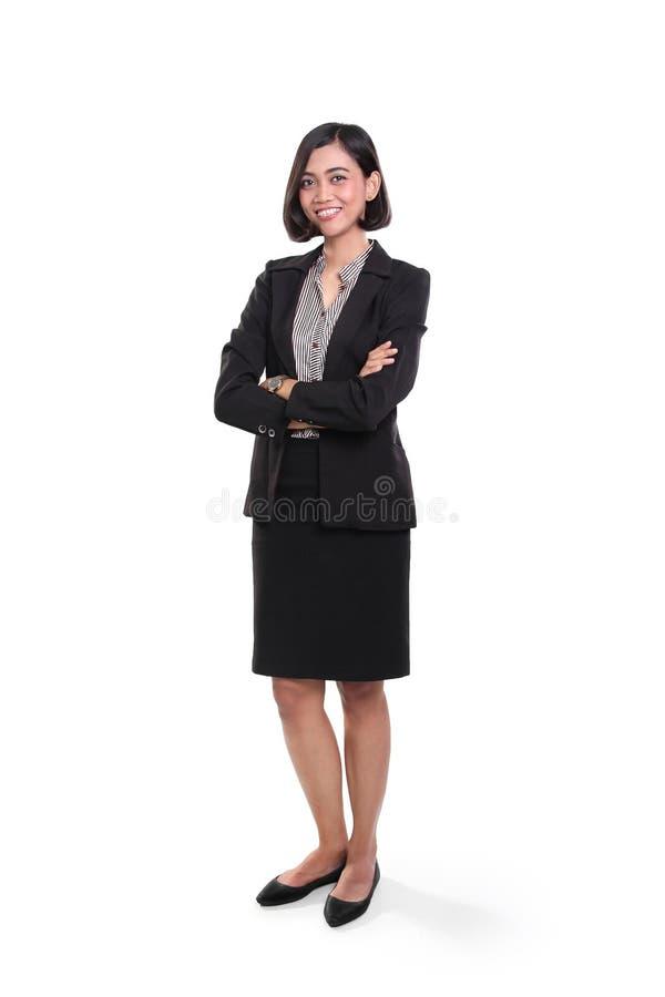 Überzeugte Geschäftsfrau, die mit den Armen gefaltet steht stockbilder