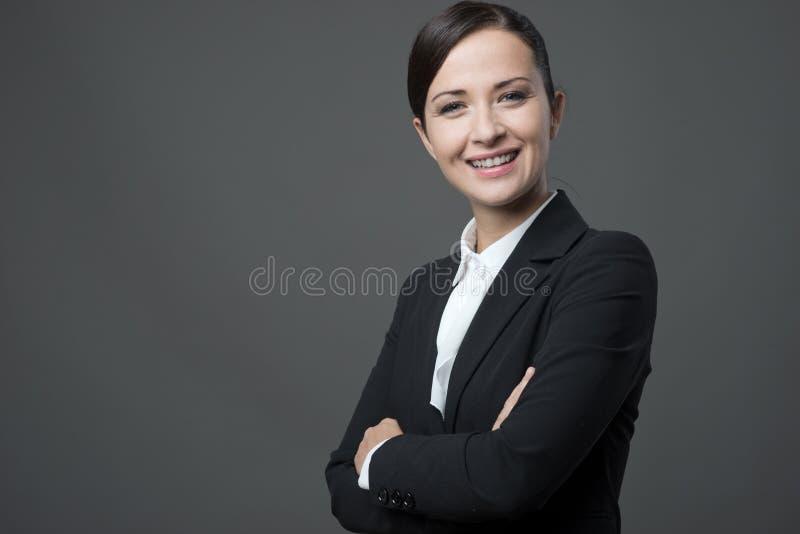 Überzeugte Geschäftsfrau, die mit den Armen gekreuzt lächelt lizenzfreie stockfotografie