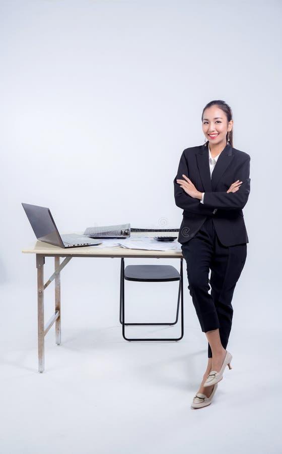 Überzeugte Geschäftsfrau im Büro lächelnd an der Kamera mit den gefalteten Armen im Büro lizenzfreies stockfoto