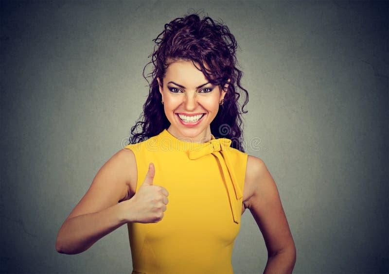 Überzeugte Geschäftsfrau im gelben Kleid, das Daumen aufgibt stockfotografie