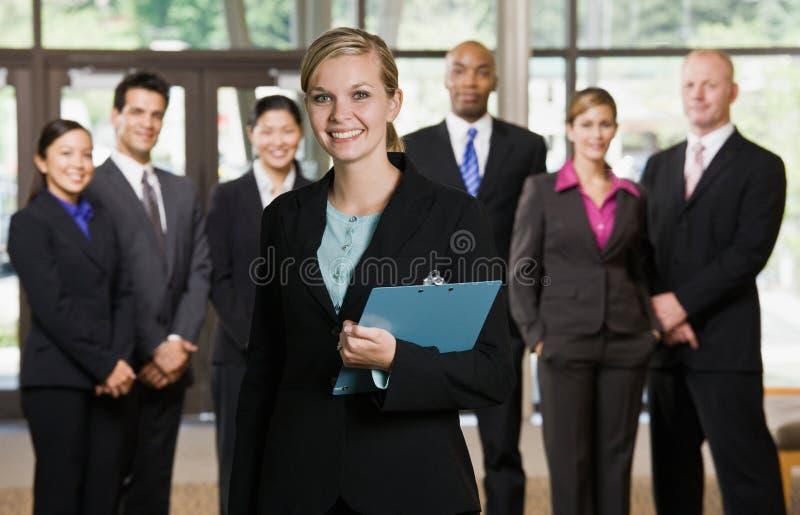 Überzeugte Geschäftsfrau vor Mitarbeitern lizenzfreies stockfoto
